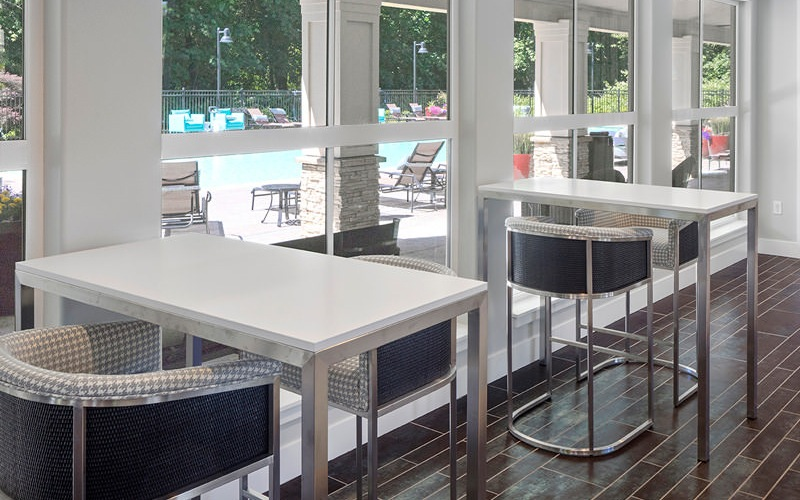 high tables and chairs in resident lounge near windows with pool views