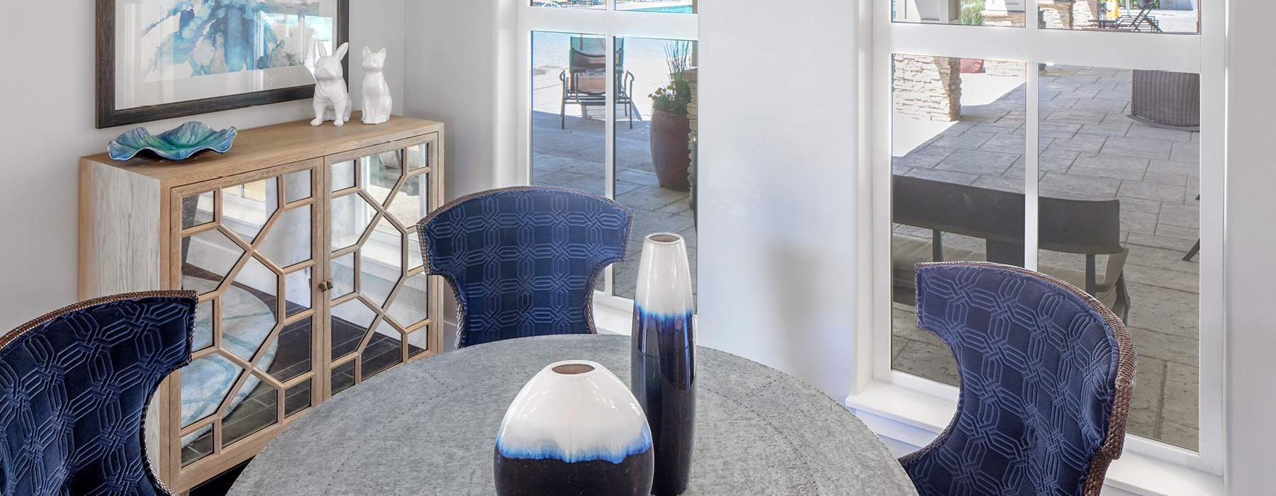 round table with chairs near large windows in resident lounge